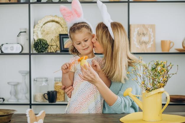 Madre con hija junto a la cocina con huevos de pascua