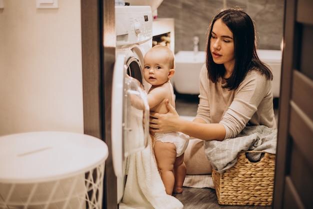 Madre con hija lavando ropa en casa