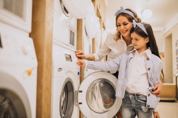 Madre con hija lavando ropa en la lavandería de autoservicio