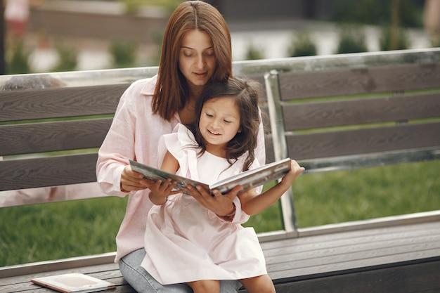 Madre con hija leyendo un libro en la ciudad