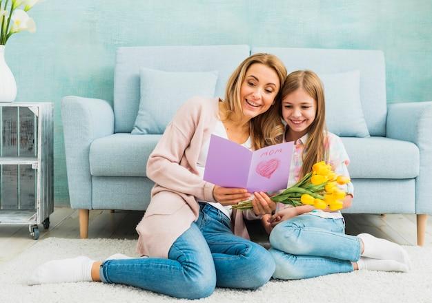 Madre con hija leyendo la postal del día de la madre.