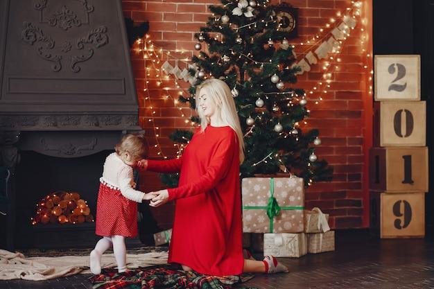 Madre con hija linda en casa en un vestido rojo