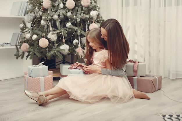 Madre con hija linda cerca del árbol de navidad