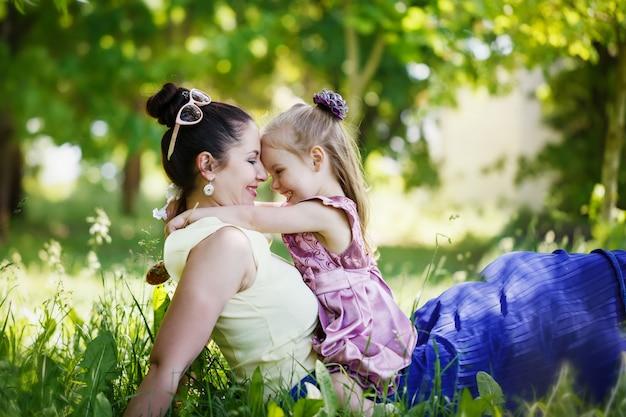 La madre y la hija se miran, sonríen, se abrazan, se sientan en una hierba en el soleado día de verano.