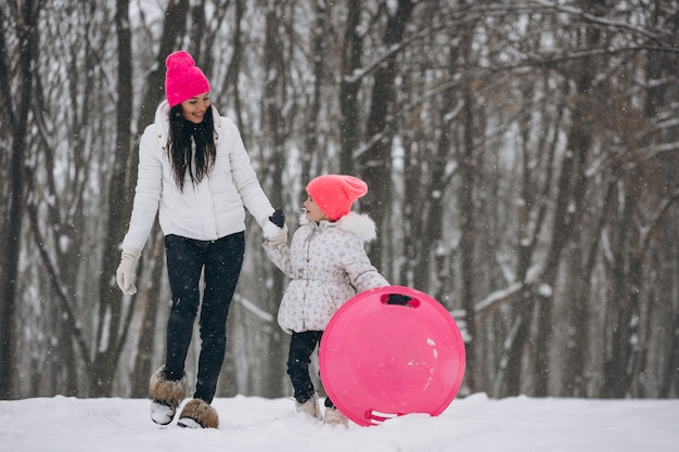 Madre con hija montando en un plato en el parque de invierno