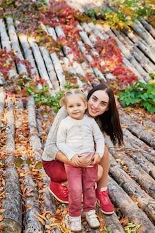 Madre con hija en el parque otoño