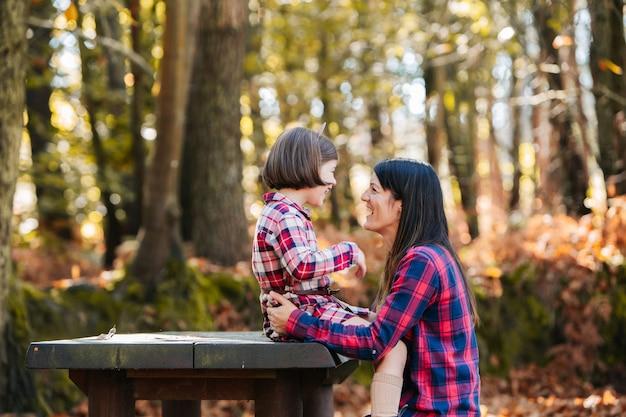 Madre con hija en el parque en otoño
