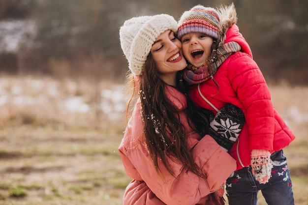 Madre con hija pequeña en un bosque de invierno