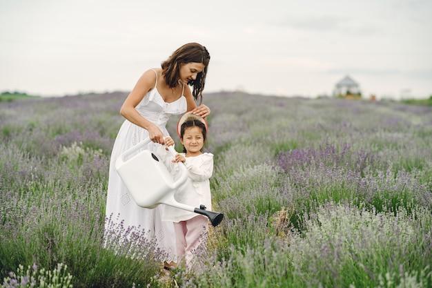Madre con hija pequeña en campo de lavanda. mujer hermosa y lindo bebé jugando en el campo del prado. vacaciones familiares en verano.