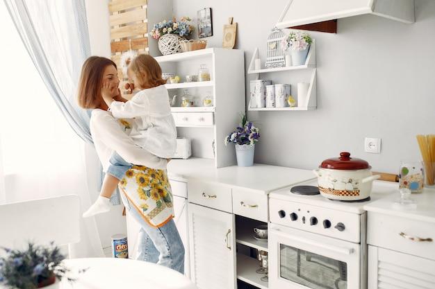 Madre con hija pequeña cocinando en casa
