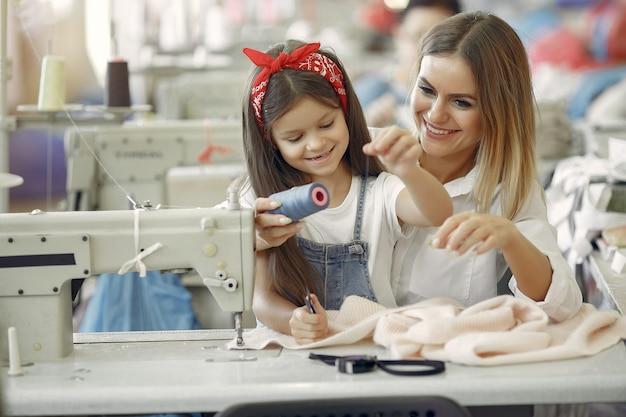 Madre con hija pequeña coser ropa en la fábrica