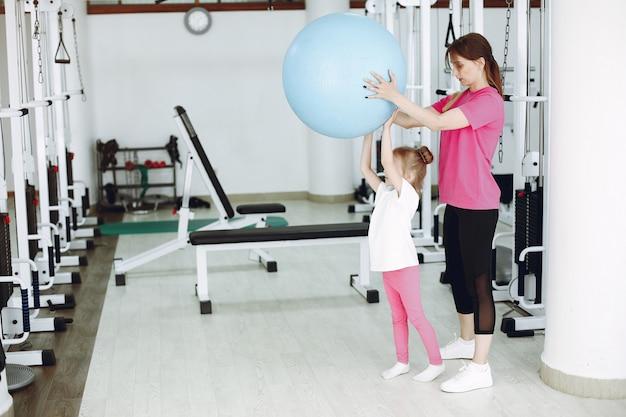Madre con hija pequeña se dedican a la gimnasia en el gimnasio.