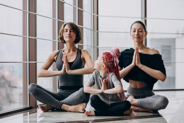 Madre con hija pequeña y entrenador practicando yoga en el gimnasio