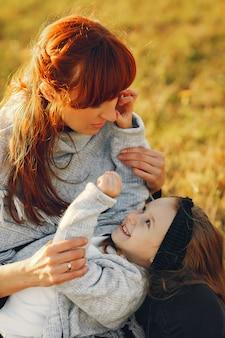 Madre con hija pequeña jugando en un campo de otoño