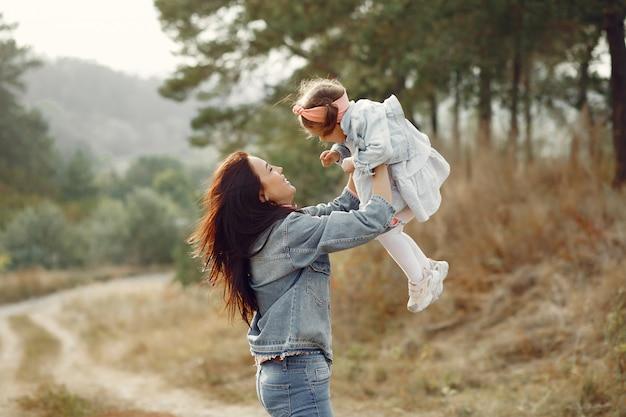 Madre con hija pequeña jugando en un campo