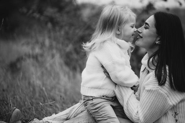 Madre con hija pequeña juntos en clima otoñal divirtiéndose