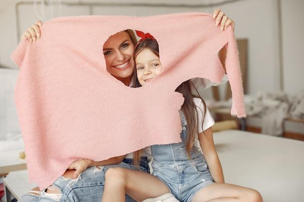 Madre con hija pequeña medir la tela para coser