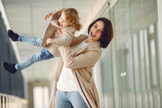 Madre con hija pequeña de pie en un pasillo