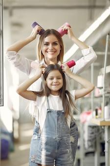 Madre con hija pequeña de pie en la tela con hilo