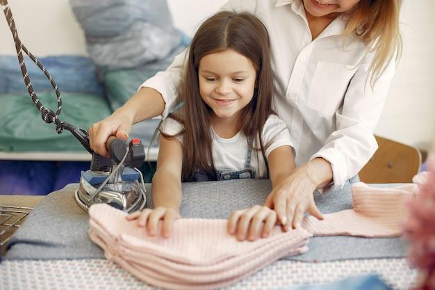 Madre con hija pequeña plancha la tela en la fábrica
