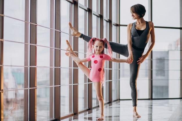 Madre con hija pequeña practicando yoga junto a la ventana