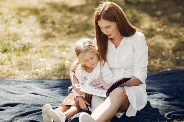 Madre con hija pequeña sentada en una tela escocesa y leer el libro