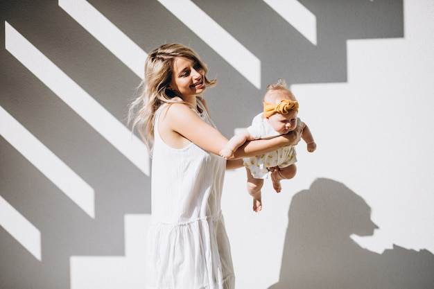 Madre con hija pequeña sobre fondo blanco.