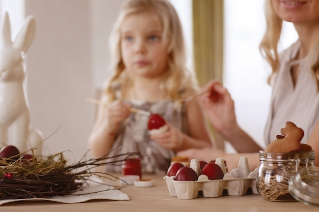 La madre y la hija pintan los huevos de pascua en el cuarto en la tabla del día de fiesta.