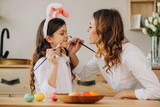 Madre con hija pintando huevos para pascua