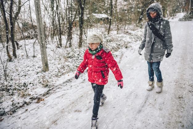Madre con hija senderismo en bosque nevado