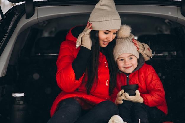 Madre con hija sentada en coche en invierno