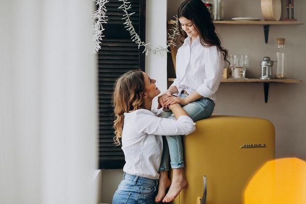 Madre con hija sentada en la cocina