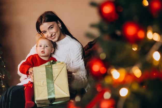 Madre con hija sentada junto al árbol de navidad