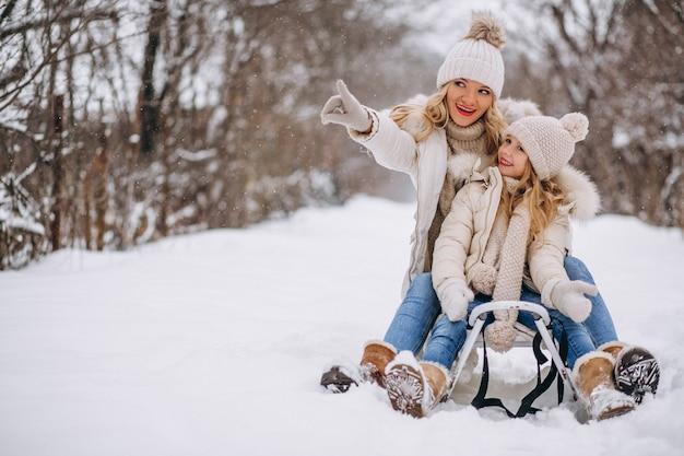 Madre con hija trineo afuera en invierno