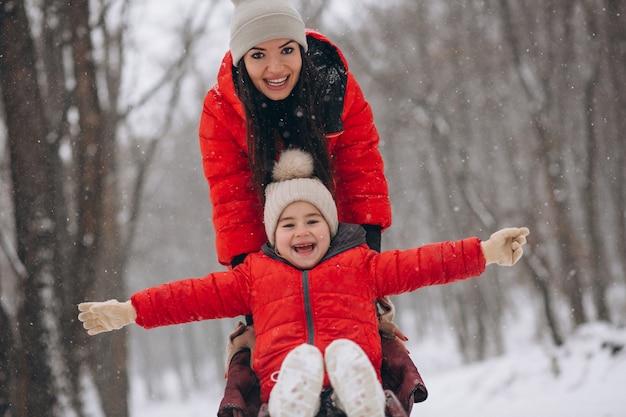 Madre con hija en trineo de parque de invierno