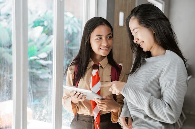 Madre hija usando tableta juntos en casa