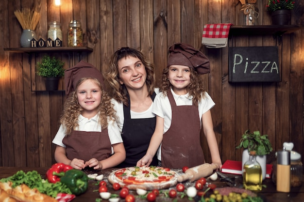 Madre con hijas cocinando pizza en la cocina