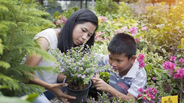 La madre y el hijo asiáticos cuidan de los árboles en el jardín.