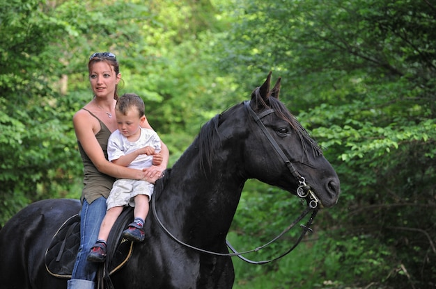 Madre, hijo y caballo negro