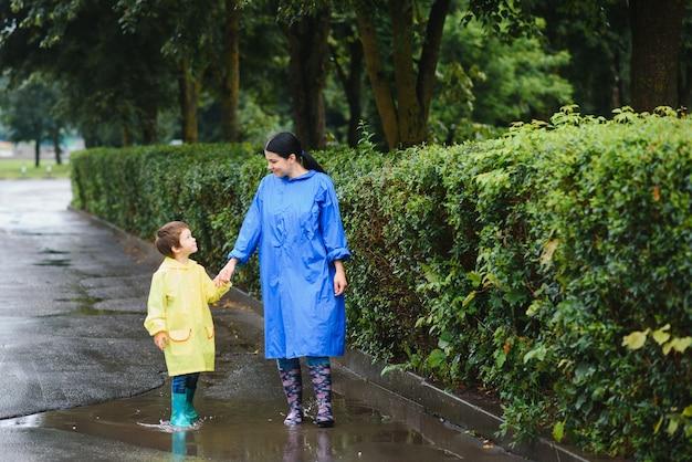 Madre con hijo caminando en el parque bajo la lluvia con botas de goma