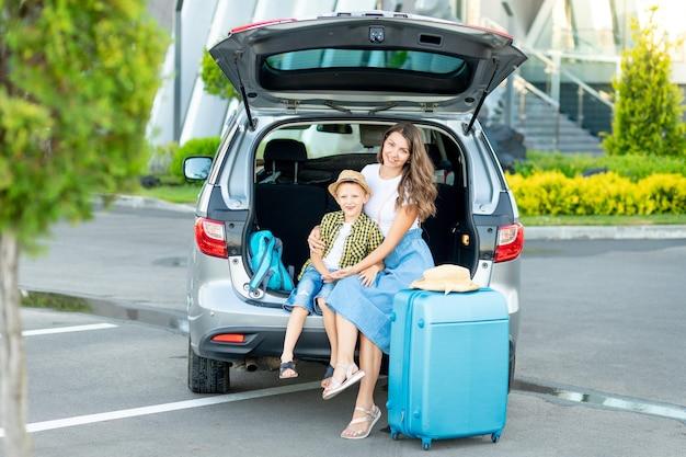 Una madre con un hijo en el coche y una maleta azul se van de vacaciones o un viaje sentado frente al aeropuerto.