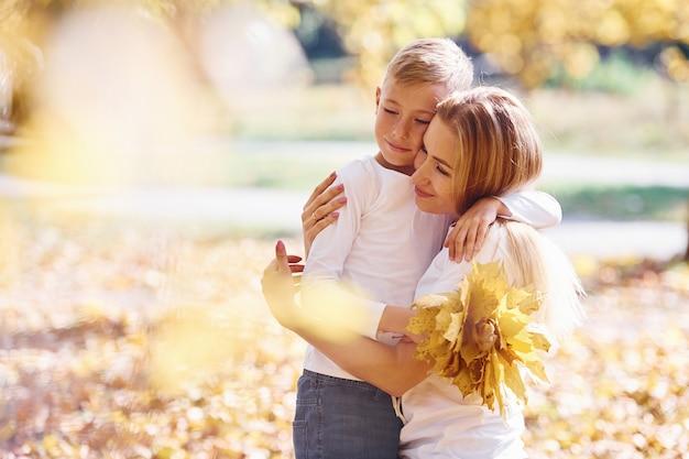 Madre con hijo descansar en un hermoso parque de otoño en un día soleado.