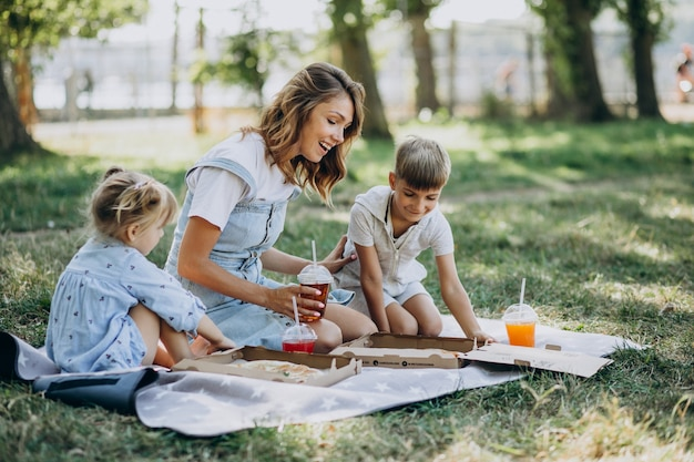 Madre con hijo e hija comiendo pizza en el parque