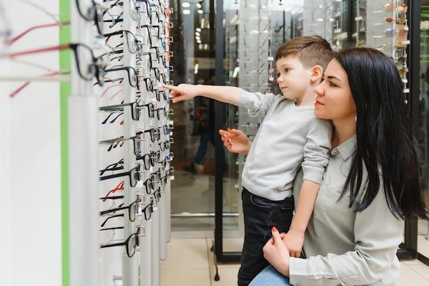 Madre con hijo eligiendo gafas en la tienda de óptica.