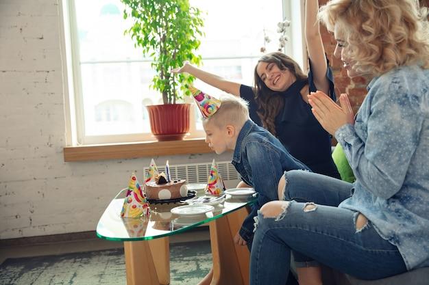 Madre, hijo y hermana en casa divirtiéndose, comodidad y acogedora celebración de cumpleaños