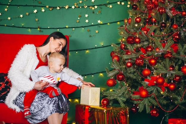 Madre con hijo junto al arbol de navidad.