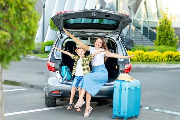 Una madre con un hijo y una maleta azul se va de vacaciones o de viaje sentada en un automóvil frente al aeropuerto con las manos extendidas como un avión