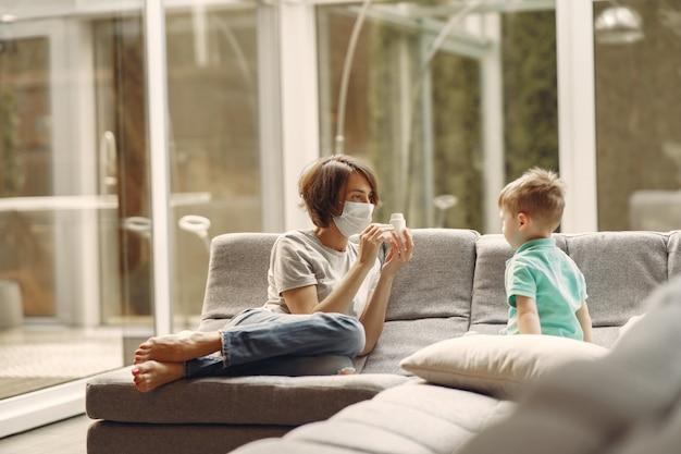 Madre con un hijo más pequeño sentado en su casa en cuarentena
