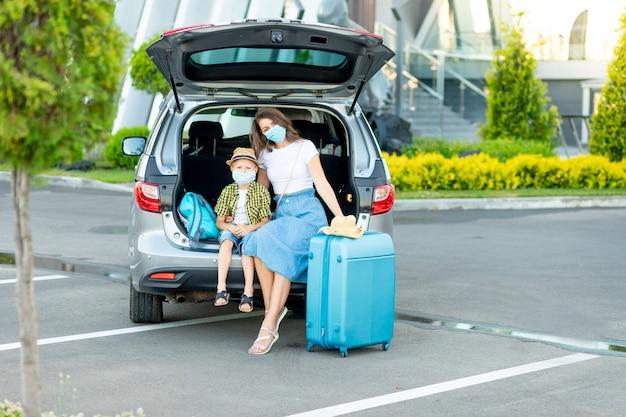 Una madre con un hijo con máscaras médicas en el automóvil y una maleta azul se va de vacaciones o de viaje sentada frente al aeropuerto