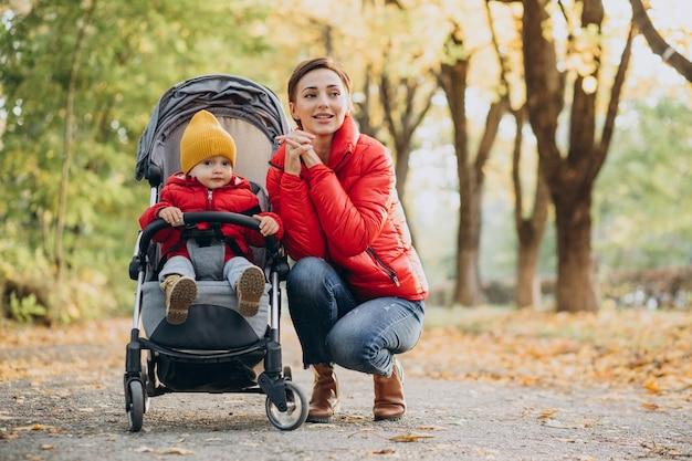 Madre con hijo pequeño en cochecito de bebé caminando en el parque otoñal
